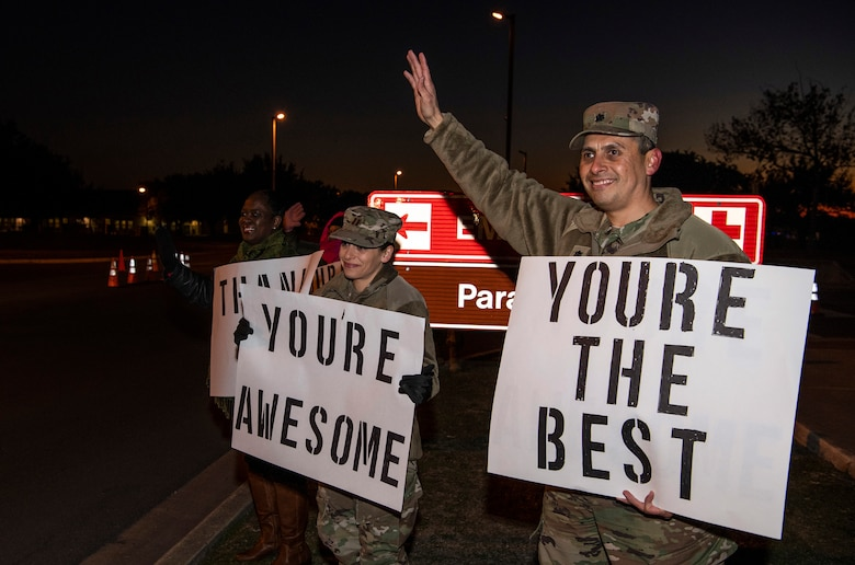 """From right, Lt. Col. Raymundo Vann, 323rd Training Squadron commander, Capt. Jessica Stanley, 737th Training Group and Lydia Davidson, wife of Col. Isaac Davidson, Inter-American Air Forces Academy commandant, hold positive messages of support at a base gate during the morning inbound commute as part of their new initiative, """"We Care,"""" at Joint Base San Antonio-Lackland, Texas, Dec. 18, 2019. The initiative involved 37th Training Wing military and civilian members spending the morning at various gates letting each person know that they stand together in support of those struggling with depression and thoughts of suicide by holding a positive message of support and handing out over 400 candy canes. If you are struggling with thoughts of suicide, please go directly to the Mental Health Clinic or to your closest Emergency Room. You can also reach the National Suicide Prevention Lifeline at 1-800-273-8255."""