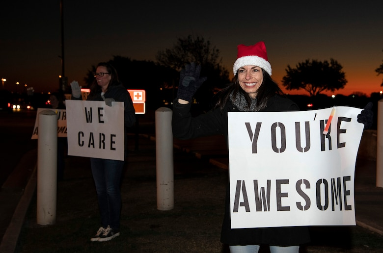 """Leslie Janaros, 37th Training Wing key spouse mentor and wife of Col. Jason Janaros, 37th TRW commander, holds a positive message of support at a base gate during the morning inbound commute as part of their new initiative, """"We Care,"""" at Joint Base San Antonio-Lackland, Texas, Dec. 18, 2019. The initiative involved 37th Training Wing military and civilian members spending the morning at various gates letting each person know that they stand together in support of those struggling with depression and thoughts of suicide by holding a positive message of support and handing out over 400 candy canes. If you are struggling with thoughts of suicide, please go directly to the Mental Health Clinic or to your closest Emergency Room. You can also reach the National Suicide Prevention Lifeline at 1-800-273-8255."""