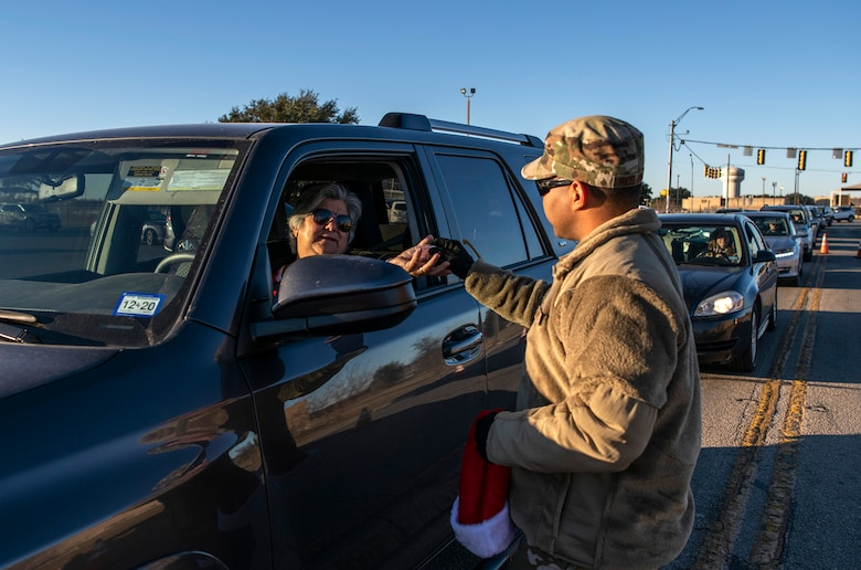 """Staff Sgt. Henin Rios Arauz, Inter-American Air Forces Academy, hands out a candy cane during the morning inbound commute in support of the 37th Training Wing new initiative, """"We Care,"""" at Joint Base San Antonio-Lackland, Texas, Dec. 18, 2019. The initiative involved 37th Training Wing military and civilian members spending the morning at various gates letting each person know that they stand together in support of those struggling with depression and thoughts of suicide by holding a positive message of support and handing out over 400 candy canes. If you are struggling with thoughts of suicide, please go directly to the Mental Health Clinic or to your closest Emergency Room. You can also reach the National Suicide Prevention Lifeline at 1-800-273-8255."""