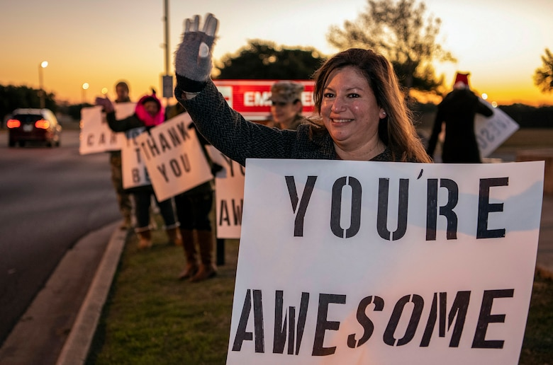 """Jennifer Vann, """"We Care,"""" organizer and wife of Lt. Col. Raymundo Vann, 323rd Training Squadron commander, holds a positive message of support at a base gate during the morning inbound commute as part of their new initiative, """"We Care,"""" at Joint Base San Antonio-Lackland, Texas, Dec. 18, 2019. The initiative involved 37th Training Wing military and civilian members spending the morning at various gates letting each person know that they stand together in support of those struggling with depression and thoughts of suicide by holding a positive message of support and handing out over 400 candy canes. If you are struggling with thoughts of suicide, please go directly to the Mental Health Clinic or to your closest Emergency Room. You can also reach the National Suicide Prevention Lifeline at 1-800-273-8255."""