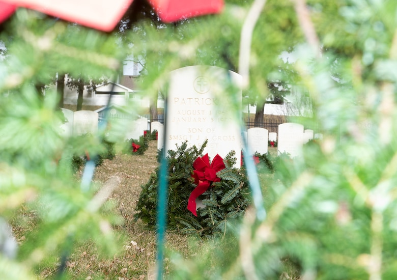 A wreath leans on a headstone at Offutt Air Force Base, Neb., Dec. 14, 2019. Wreaths were placed on each headstone and eight ceremonial wreaths honored the four armed services, the Coast Guard, the Merchant Marines, POW/MIA, and the 22 veterans and active duty service members who take their lives each day.