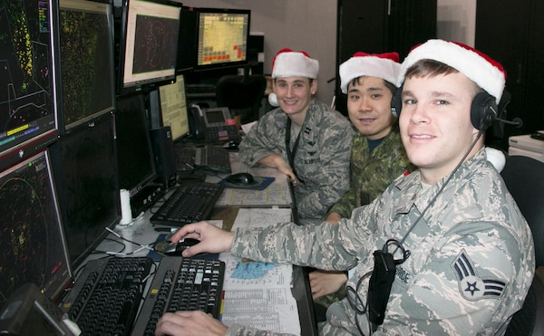 Airmen at the Eastern Air Defense Sector (EADS) train in preparation for Santa's Christmas Eve flight at EADS headquarters in Rome, N.Y., Dec. 17, 2019. Pictured are, from right,  Senior Airman Timothy Destito of the New York Air National Guard; Capt. John Byeon, Royal Canadian Air Force, and Capt. Sarah Atherton, New York Air National Guard. Atherton and Destito are members of the 224th Air Defense Squadron and  Byeon is a member of the Canadian Detachment at EADS.