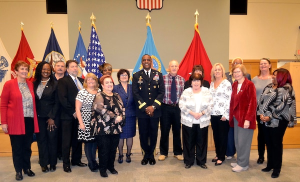 16 Civilian retirees pose with the Defense Logistics Agency Troop Support commander at a retirement ceremony.
