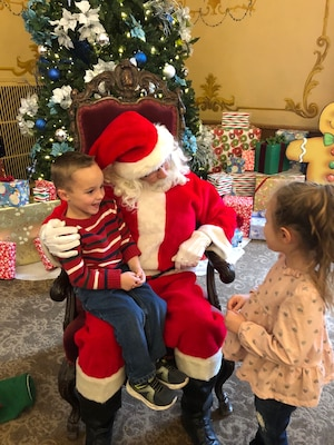A boy sits on Santa's lap while a girl stands in front.