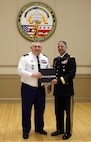 Maj. Gen. Olivier Kim, Chief of the French Gendarmerie Reserves Command, presents a historical photobook to Brig. Gen. Aaron R. Dean II, the Adjutant General of the District of Columbia National Guard, at the conclusion of his visit to the DCNG Armory.