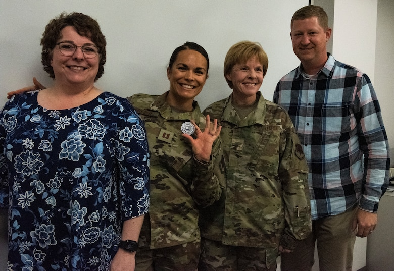 U.S. Air Force Capt. Alissa Brewer, 325th Operational Medical Readiness Squadron dentist, center, poses for a photo with her mother, left, her husband, right, and U.S. Air Force Brig. Gen. Sharon Bannister, Air combat Command Surgeon General, at Tyndall Air Force Base, Florida, Dec. 20, 2019. Brewer holds a coin presented to her by the general for her hard work and dedication to unit success. (U.S. Air Force photo by Staff Sgt. Magen M. Reeves)