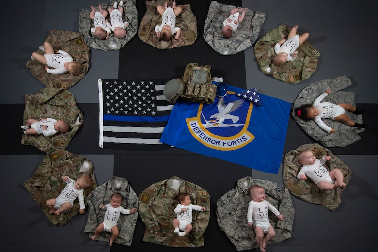 Thirteen babies lay on their parents uniforms Nov. 20, 2019, at Mountain Home Air Force Base, Idaho. The U.S. Air Force has annouced 2019 as the Year of the Defender in honor of security forces members. (U.S. Air Force photo by Airman Natalie Rubenak)
