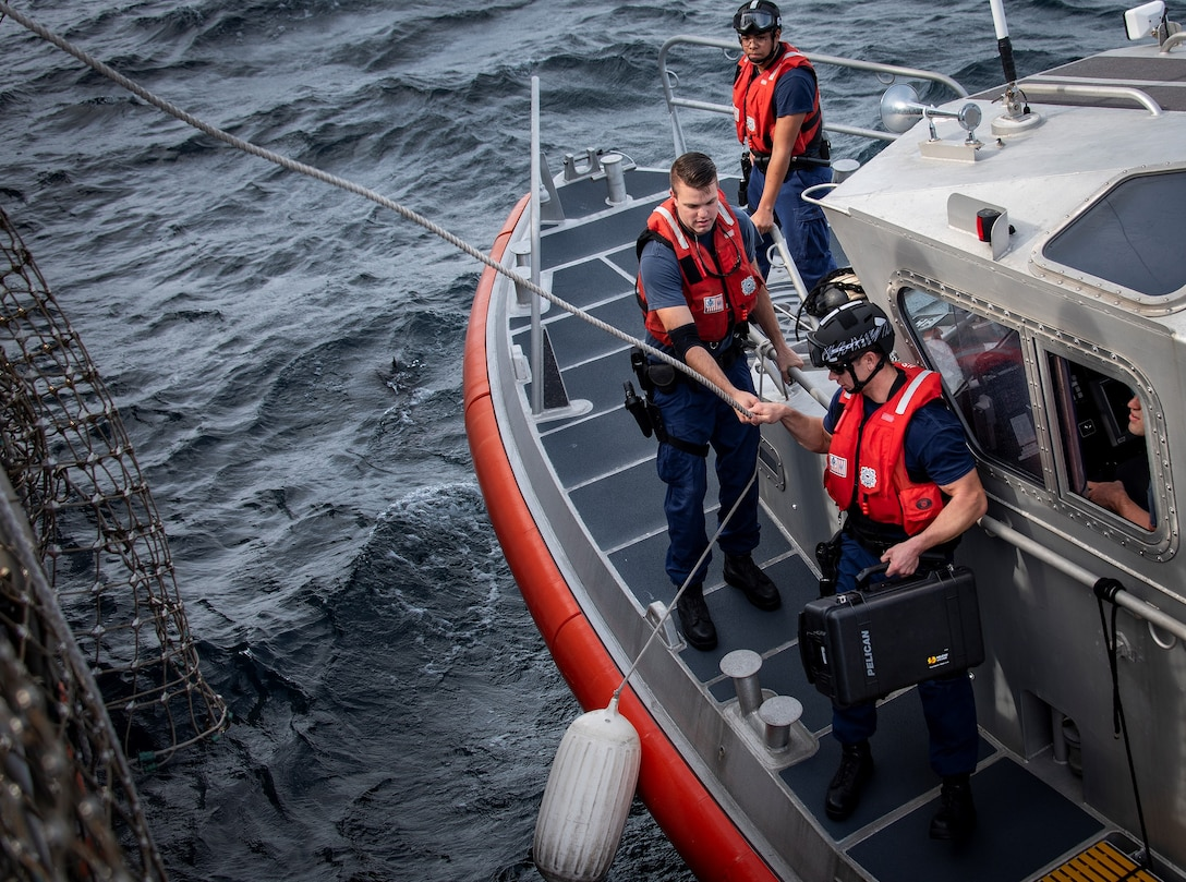 Coast Guardsmen secure communications equipment to a line to bring it aboard USS Thomas Hudner (DDG 116) in the Gulf of Mexico Dec. 16, 2019. The Navy used that equipment during the first demonstration of the Advanced Battle Management System, operators across the Air Force, Army, Navy and industry tested multiple real-time data sharing tools and technology in a homeland defense-based scenario enacted by U.S. Northern Command and enabled by Air Force senior leaders at Eglin Air Force Base, Fla., Dec. 16-18. (U.S. Air Force photo by 2nd Lt. Karissa Rodriguez)