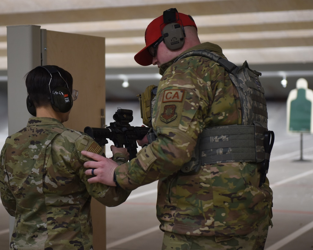 Staff Sgt. Britton Smith, 460th Security Forces Squadron combat arms instructor, teaches Chief Master Sgt. Jeannie Sousa, 460th Medical Group superintendent, how to properly hold a weapon at the 460th Security Forces Combat Arms Training and Maintenance facility at Buckley Air Force Base, Colo., Dec. 19, 2019.