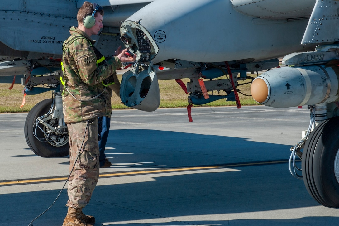 Photo of an Airmen inspecting a gas cap