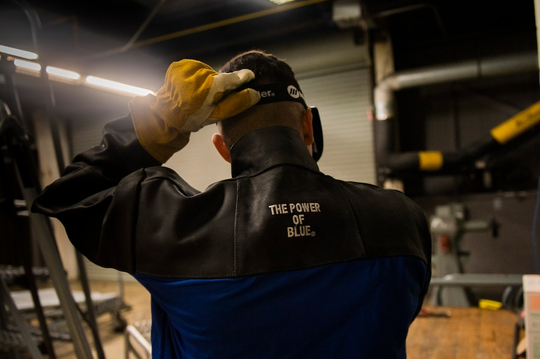 A photo of an Airman putting on a protective mask