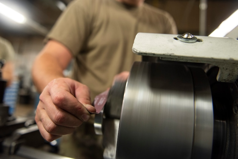 A photo of an Airman using sandpaper to smooth a bushing while it's rotating.