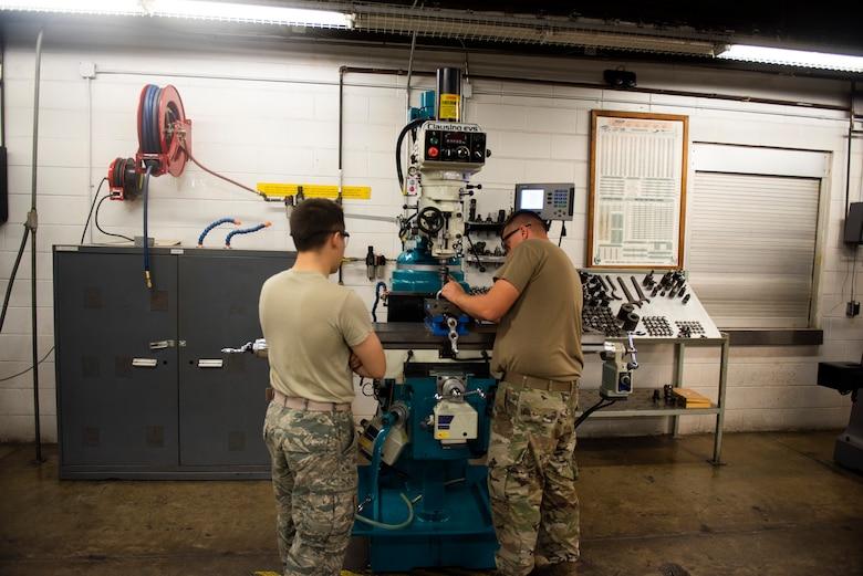 A photo of Airmen preparing to drill a bushing
