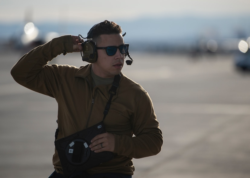 An Airman adjusts his headset while holding a tablet.