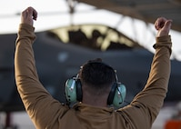 An Airman lifts his hands above his head to signal a pilot in a F-35A Lightning II fighter jet.