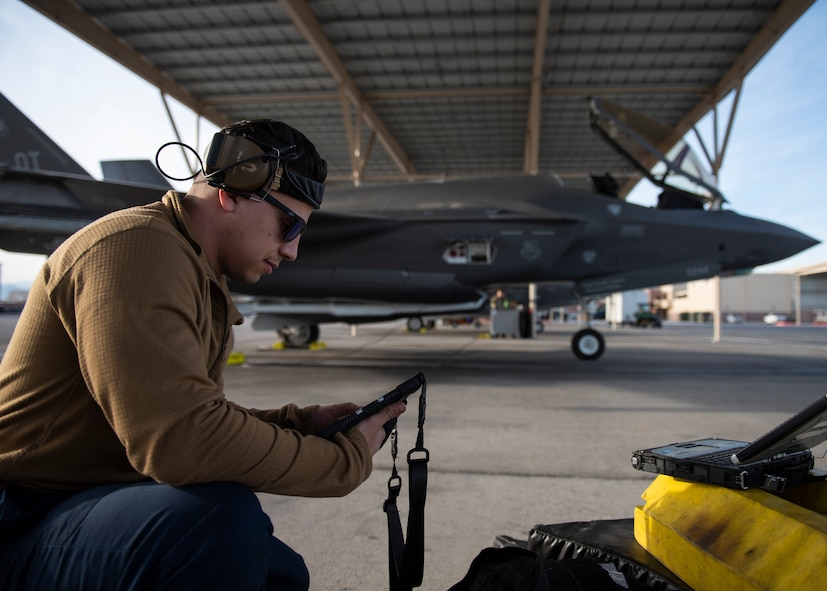 An Airman holds a tablet with an F-35A Lightning II fighter jet in the background.