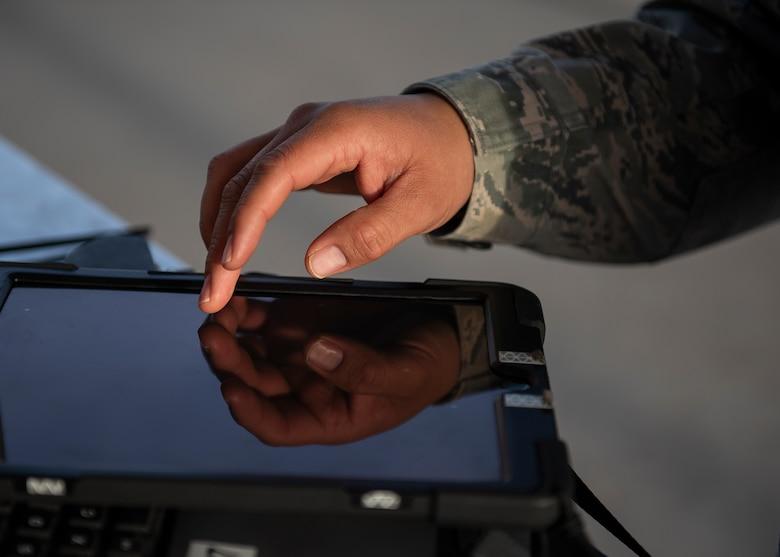 An Airmen touches a tablet.