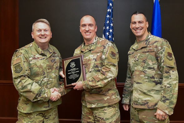Col. Max Pearson, 480th Intelligence, Surveillance and Reconnaissance Wing commander, and Chief Master Sgt. Robert Walker, 480th ISRW command chief (right), present Senior Master Sgt. Jakob Kurtz, 480th ISRW safety superintendent, the Air Combat Command Safety Career Professional of the Year award at Joint Base Langley-Eustis, Virginia, Dec. 17, 2019. By understanding different aspects of every Air Force career field within the wing, Kurtz was able to identify job hazards and make the proper corrections. (U.S. Air Force photo by Tech. Sgt. Darnell T. Cannady)