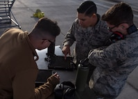 Three Airmen huddle around a tool box with a tablet laying on top of it.