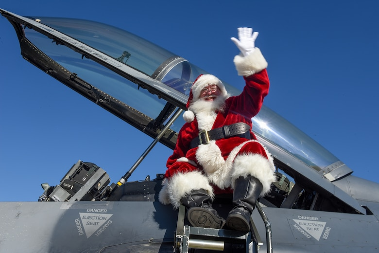 Santa Claus waves as he arrives in an F-16 Fighting Falcon