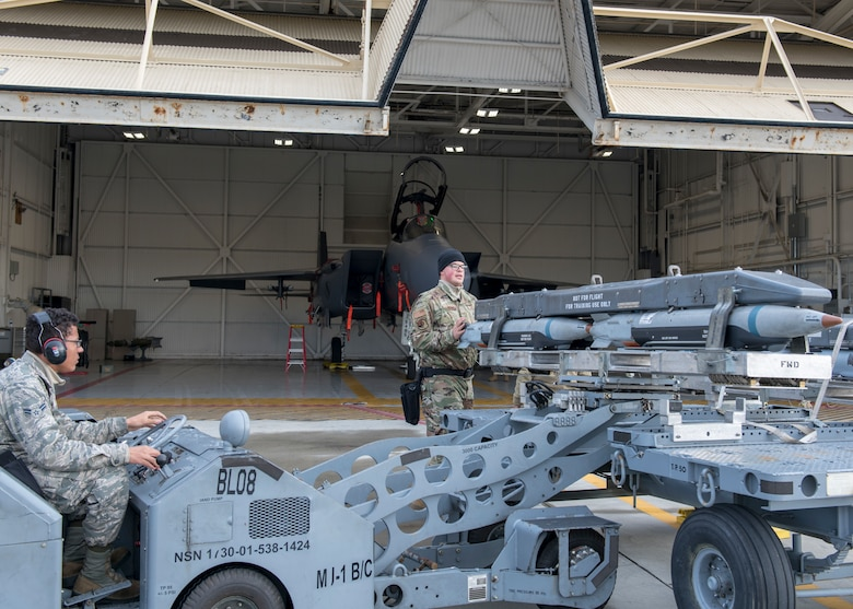 Airman 1st Class and AMU load crew technician work together to load a Bomb Rack Unit 61 on an MJ-1 lift truck