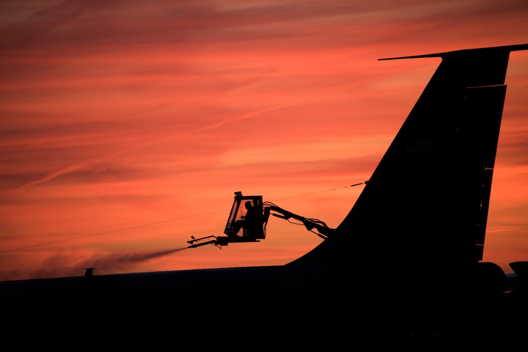 Tech. Sgt. de-ices an aircraft early in the morning