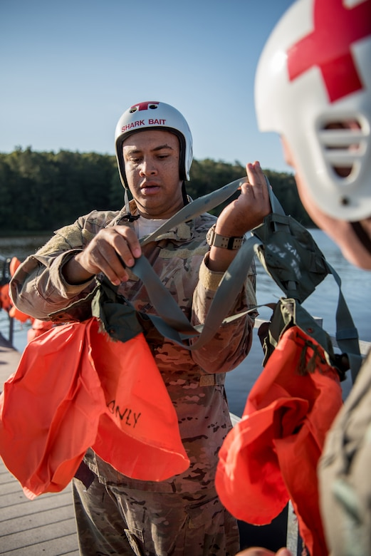 Staff Sgt. Kierre Brown, a loadmaster for the Kentucky Air National Guard's 165th Airlift Squadron, straps on a parachute harness prior to water survival training at Camp Crooked Creek in Shepherdsville, Ky., Sept. 14, 2019. The training also covered land survival techniques and orienteering. (U.S. Air National Guard photo by Staff Sgt. Joshua Horton)