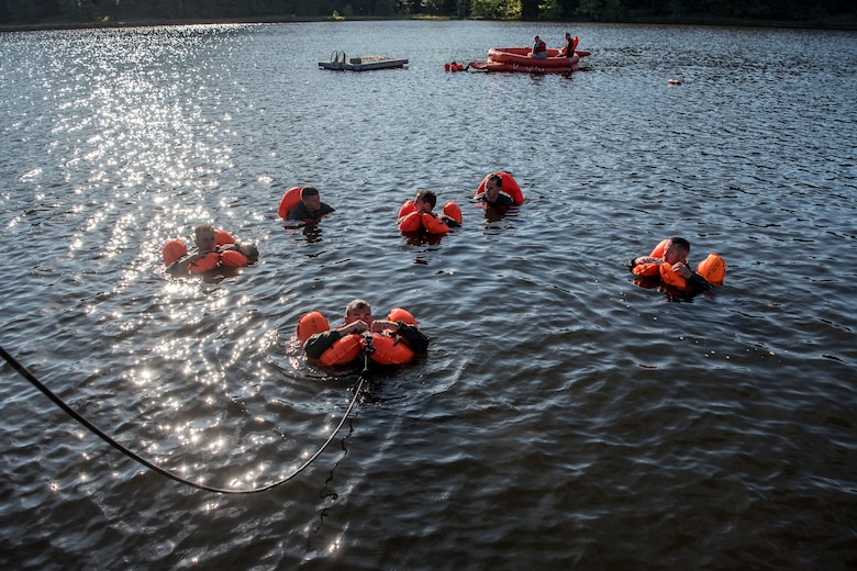 Aircrew members from the Kentucky Air National Guard's 123rd Airlift Wing are pulled to land after extricating themselves from underneath a floating parachute during water survival training at Camp Crooked Creek in Shepherdsville, Ky., Sept. 14, 2019. The training also covered land survival techniques and orienteering. (U.S. Air National Guard photo by Staff Sgt. Joshua Horton)