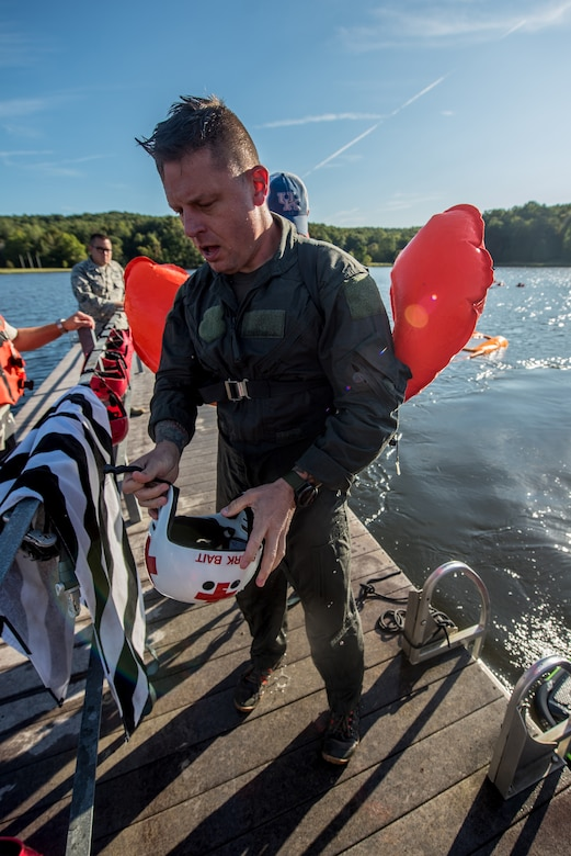 Master Sgt. Darren Wiles, a loadmaster for the Kentucky Air National Guard's 123rd Contingency Response Group, removes his personal protective equipment after being pulled across the water at Camp Crooked Creek in Shepherdsville, Ky., Sept. 14, 2019, by a personal watercraft as part of routine survival training. The exercise is designed to simulate what could happen to aircrew members who've parachuted into water when the wind catches their open chutes and drags them across the surface, posing the risk of drowning. (U.S. Air National Guard photo by Staff Sgt. Joshua Horton)