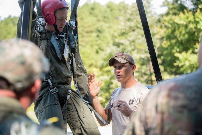 Master Sgt. Matthew Cothron (right), a Survival, Evasion, Resistance and Escape instructor for the Kentucky Air National Guard's 123rd Special Tactics Squadron, briefs aircrew members from the 165th Airlift Squadron on how to lower themselves from a training apparatus during survival training at Camp Crooked Creek in Shepherdsville, Ky., Sept. 14, 2019. The exercise is designed to train aircrew members on proper procedures should they become caught in a tree while parachuting to the ground. (U.S. Air National Guard photo by Staff Sgt. Joshua Horton)