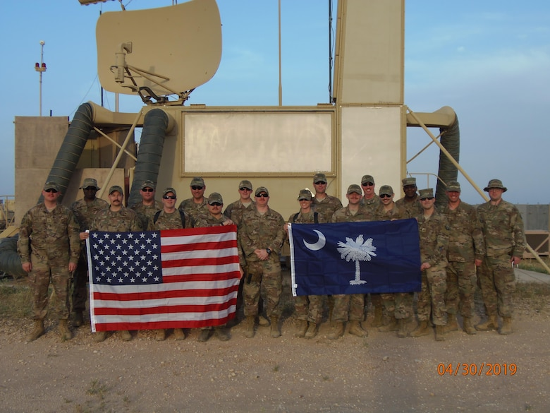 U.S. Airmen assigned to the South Carolina Air National Guard's 245th Air Traffic Control Squadron pose with two flags during their deployment to Al Asad Airbase in Iraq, April 30, 2019. (U.S. Air National Guard courtesy photo)