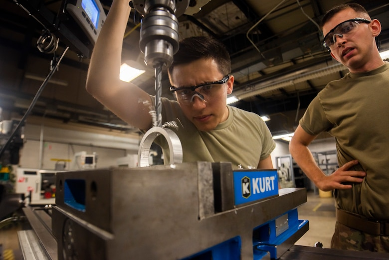 A photo of Airmen drilling into a bushing