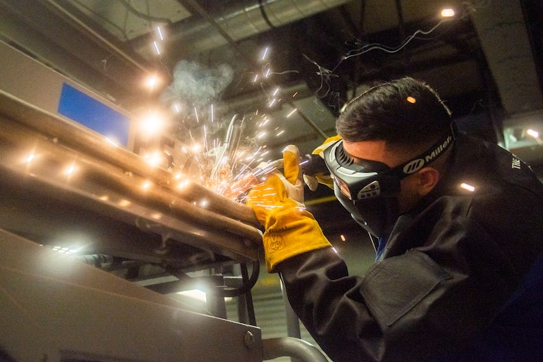 A photo of an airman welding while sparks fly.