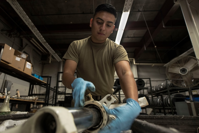 Airman cleans aircraft part