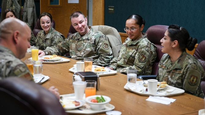 Chief Sharp, AFSC command chief, sits at a table with other Airmen at a table while they eat breakfast.