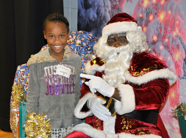 """A student visits with Santa Claus Dec. 19 during the annual """"Spread the Joy"""" event sponsored by the Air Force Civil Engineer Center Emergency Management team from Tyndall Air Force Base, Fla."""