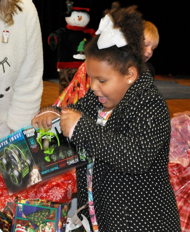 """A student from Lucille Moore Elementary School in Panama City, Florida, gasps with surprise as she opens her gift to reveal a new remote control car.  On Dec. 19, members of the Air Force Civil Engineer Center Emergency Management team at Tyndall Air Force Base, Fla., visited with the students at the school to celebrate Christmas early during the """"Spread the Joy"""" event."""