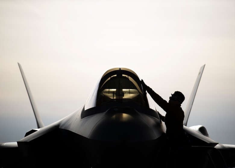 An Airman cleans the canopy of an F-35A Lighting II fighter jet.