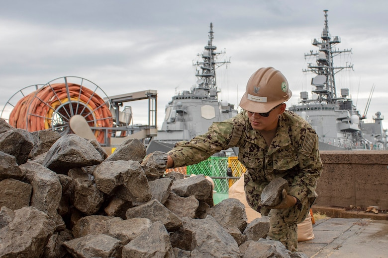 SASEBO, Japan (Oct. 28, 2019) Builder 1st Class Remie Acosta, from Lawrence, Massachusetts, and Utilitiesman 3rd Class Jaime Orobio, from Houston, both deployed with Naval Mobile Construction Battalion (NMCB) 5's Detail Sasebo, place riprap as part of the repairs underway for a section of the seawall on Commander Fleet Activities Sasebo to further improve the base's military readiness and capability. Seabees at Detail Sasebo are currently repairing a typhoon damaged the seawall to mitigate further erosion and destabilization of the adjacent Pre-Engineered Building Foundation. NMCB-5 is deployed across the Indo-Pacific region conducting high-quality construction to support U.S. and partner nations to strengthen partnerships, deter aggression, and enable expeditionary logistics and naval power projection.
