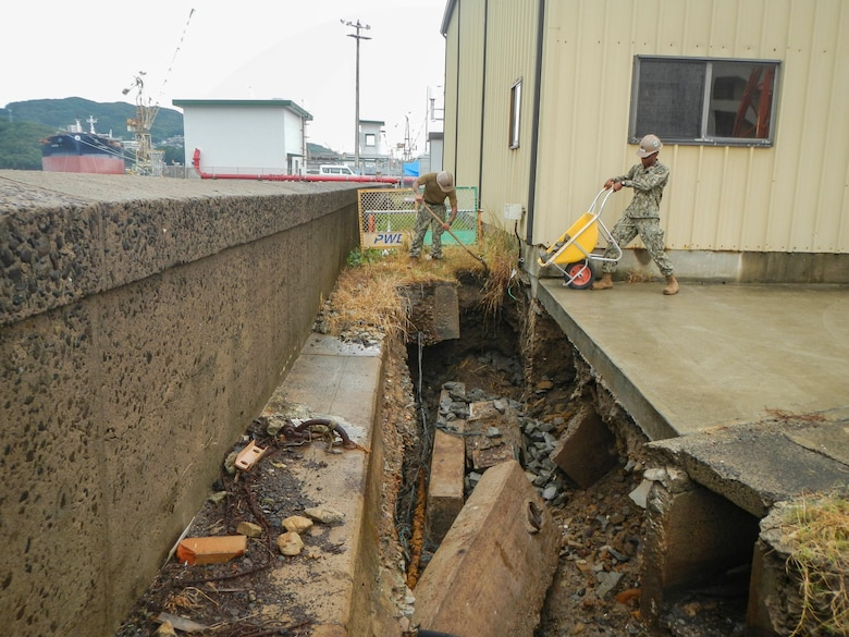 SASEBO, Japan (Oct. 28, 2019) Builder 3rd Class Lawrence Spears, from Houston, deployed with Naval Mobile Construction Battalion (NMCB) 5's Detail Sasebo, places riprap to repair critical infrastructure damage to the seawall on Commander Fleet Activities Sasebo to further improve the base's military readiness and capability.  NMCB-5 is deployed across the Indo-Pacific region conducting high-quality construction to support U.S. and partner nations to strengthen partnerships, deter aggression, and enable expeditionary logistics and naval power projection.