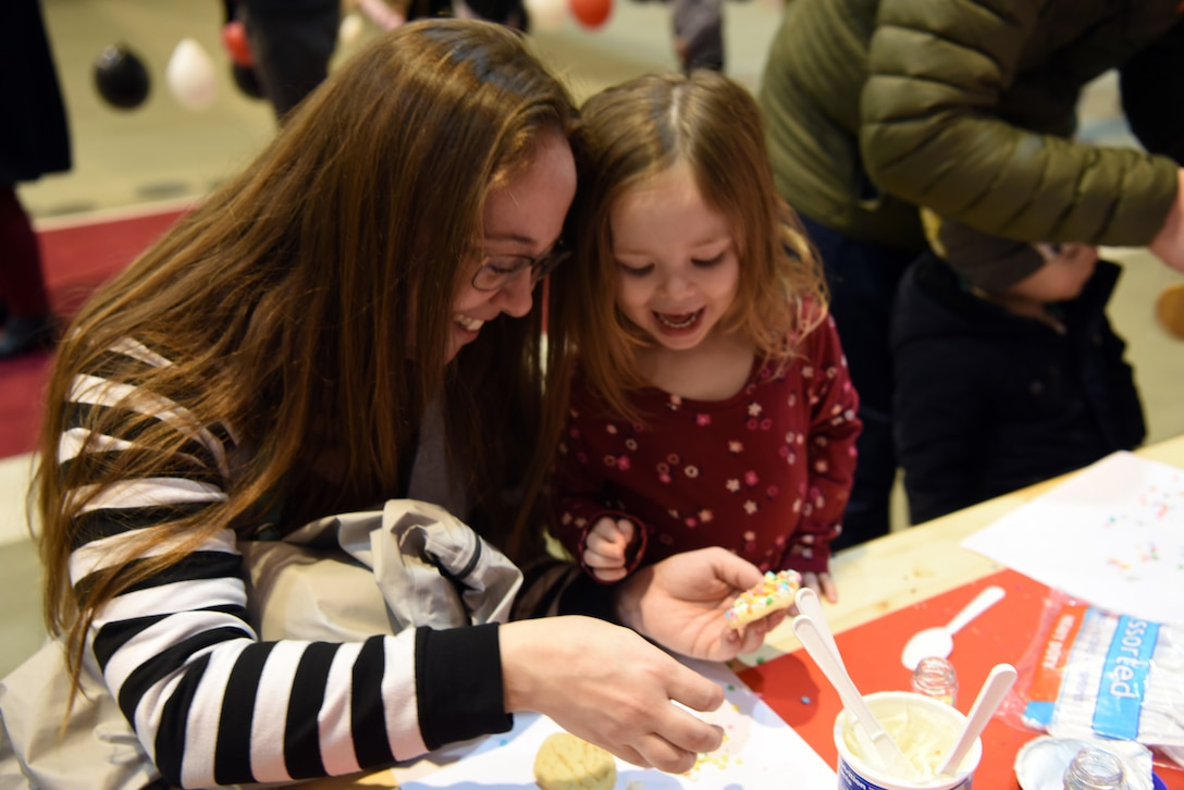 June, daughter of U.S. Air Force Capt. Daniel McKeown, 435th Contingency Response Support Squadron assistant director of operations, expresses delight as she and her mother, Margery, decorate cookies together during the Rudolph the Red Nosed Herc event at Ramstein Air Base, Germany, Dec. 20, 2019.