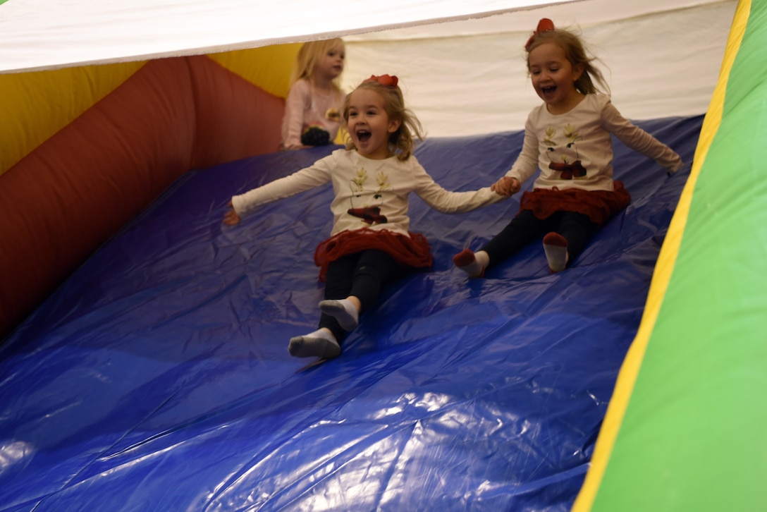 Lillian and Rylee, daughters of U.S. Air Force Maj. Casey Brown, 86th Airlift Wing, Wing Plans and Programs action officer and pilot, hold hands as they slide down an inflatable slide during the Rudolph the Red Nosed Herc event at Ramstein Air Base, Germany, Dec. 20, 2019.
