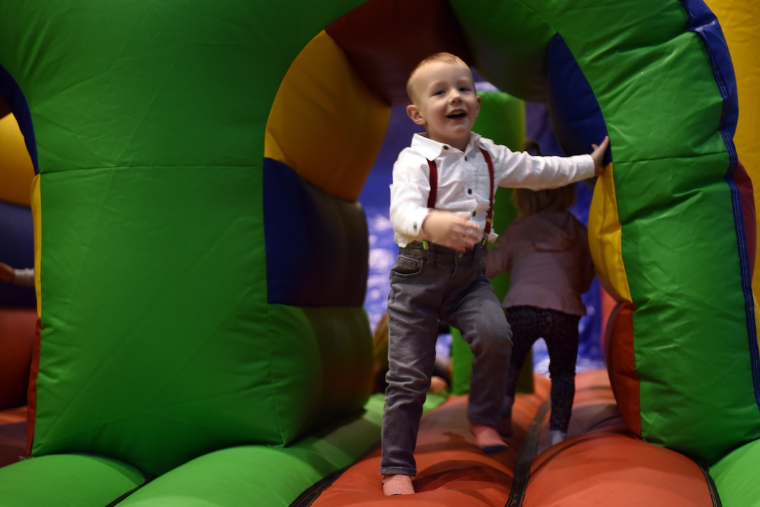 Bryson, son of Jameson Kaye, 86th Maintenance Group field service representative, plays on an inflatable slide and obstacle course during the Rudolph the Red Nosed Herc event at Ramstein Air Base, Germany, Dec. 20, 2019.