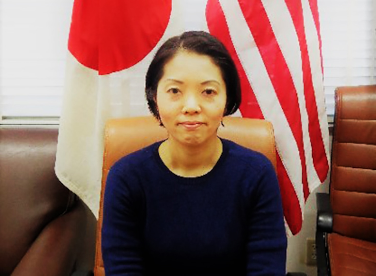 Megumi Ikeda poses in front of the Japanese and U.S. flags.