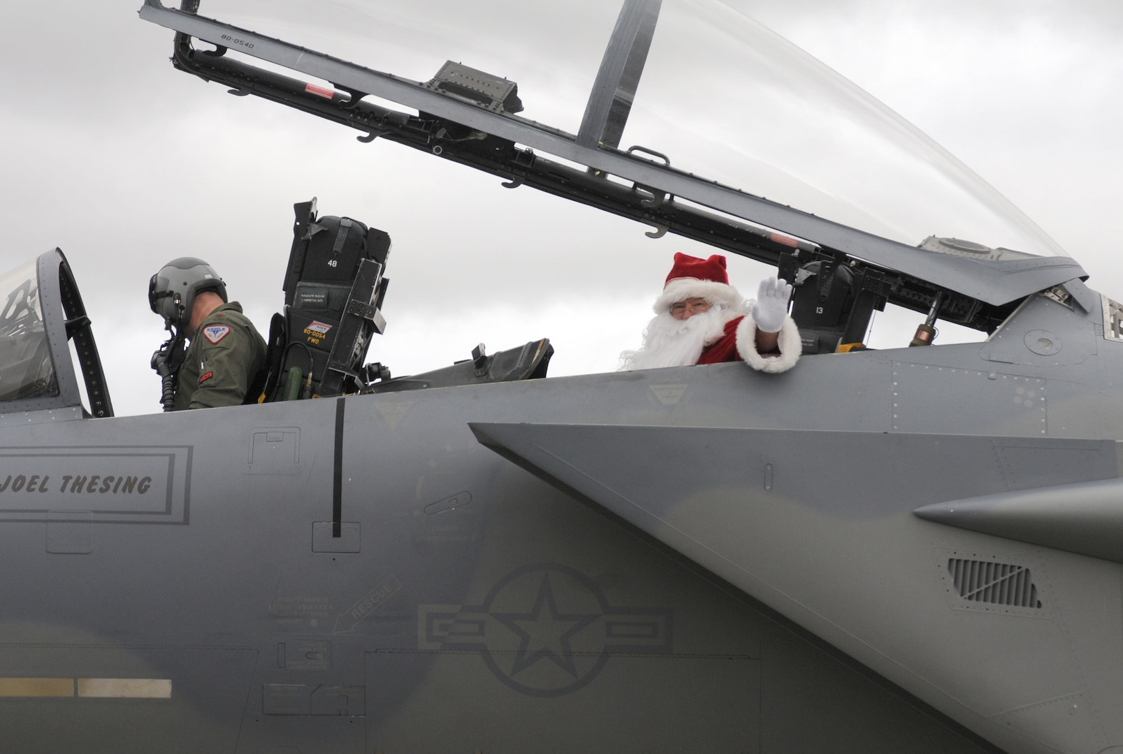 Santa Clause waves from the back seat of an F-15 Eagle