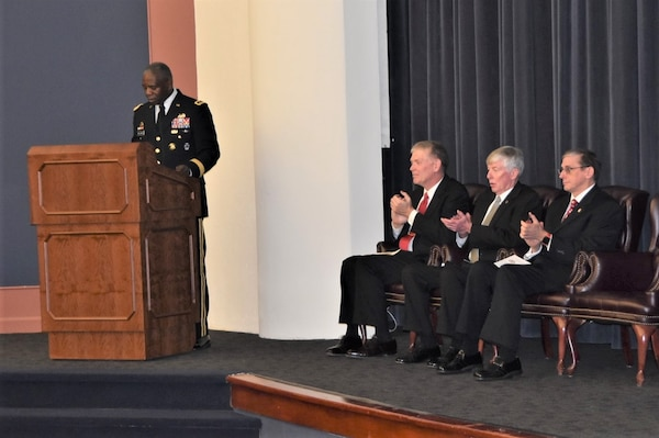 Army Lt. Gen. Darrell K. Williams stands at a lectern on stage with three Army Command and General Staff School officials seated behind him applauding
