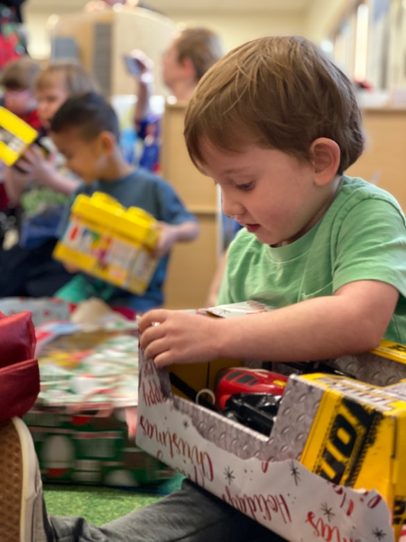 Children open their presents from Santa at the Youth & Family Services Center in Rapid City, S.D., Dec. 17, 2019. Each year, the 28th Operations Group puts together Angel Tree, collecting presents to gift to children enrolled in YFS programs. (U.S. Air Force photo by Senior Airman Michael Jones)