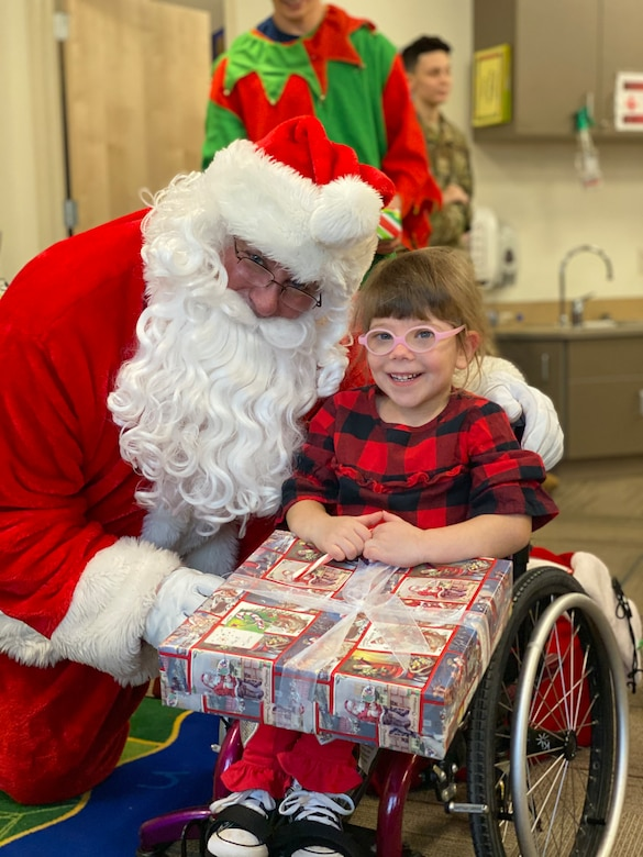 Santa poses with a child enrolled at the Youth & Family Services Center in Rapid City, S.D., Dec.17, 2019. For the past 12 years, Dave Garrett, 28th Operations Support Squadron Assistant Director of Operations, has posed as Santa, visiting the kids at the YFS Center during the 28th Operations Group's annual Angel Tree event. (U.S. Air Force photo by Senior Airman Michael Jones)