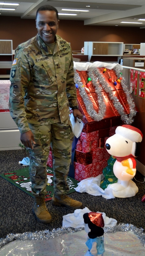 DLA Troop Support Commander Army Brig. Gen. Gavin Lawrence inspects the Peanuts-inspired display created by the Business Process Support office for a holiday decorating contest Dec. 20, 2019, in Philadelphia.