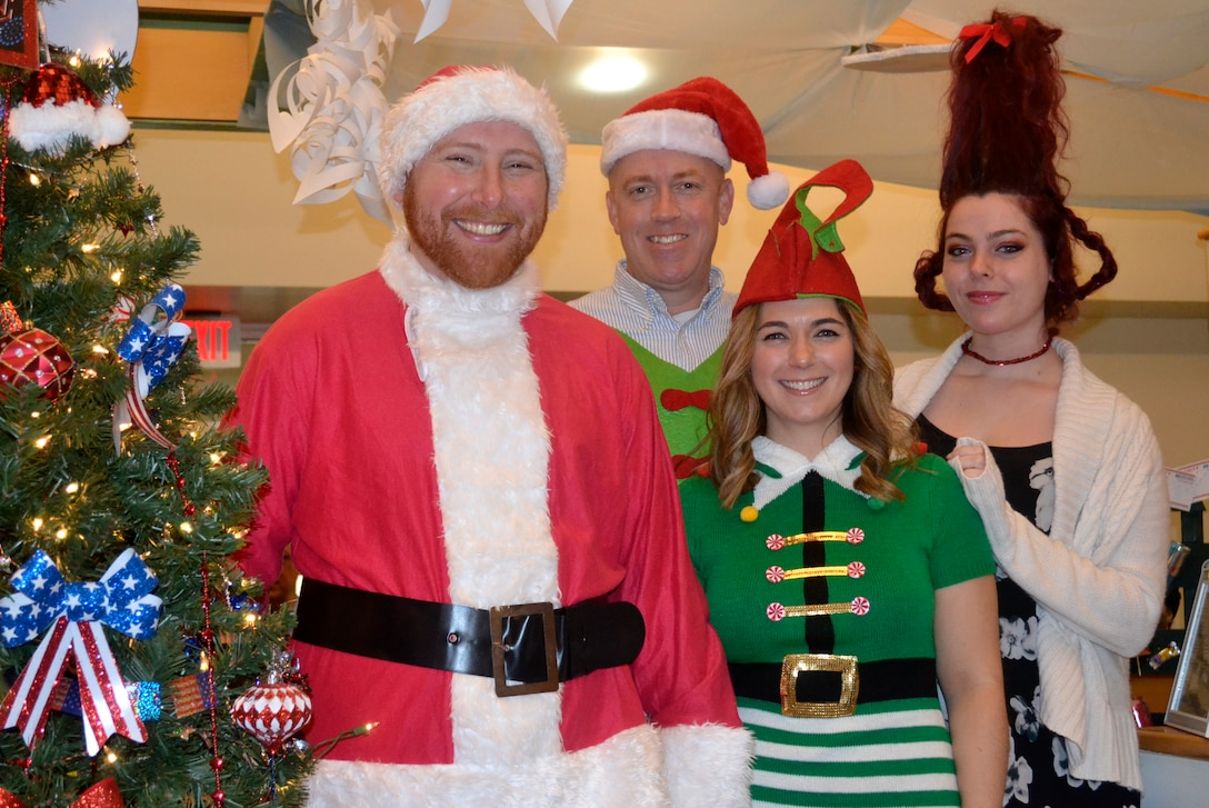 Festively costumed employees from DLA Troop Support's Subsistence supply chain pose in front of their display as a part of the annual decorating contest Dec. 20, 2019, in Philadelphia.